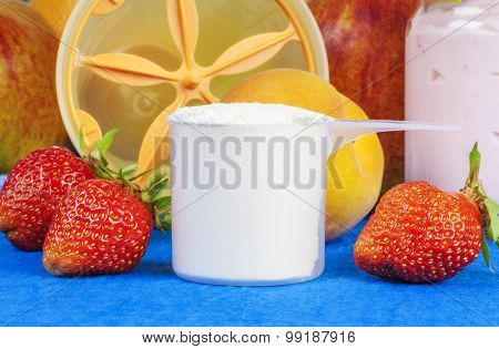 Plastic cup of protein powder with strawberries around