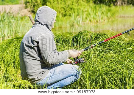 Man fishing near lake in summer