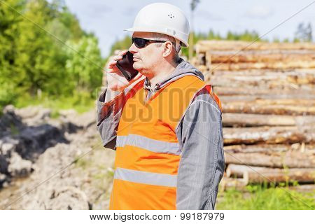 Forest officer talking on cell phone near lumber pile