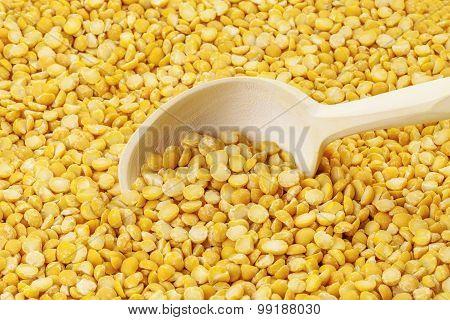 Dry split peas on wooden spoon