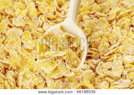 Yellow cornflakes on wooden spoon
