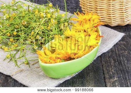 Marigold flowers in green bowl with dry chamomile