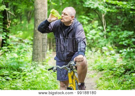 Man with bottle of water on bicycle in forest