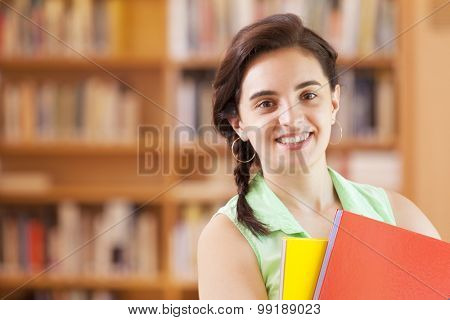Smart female student standing with notebooks at the library