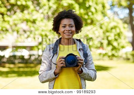 people, photography, technology, leisure and lifestyle - happy young african american female photographer with digital camera in summer park