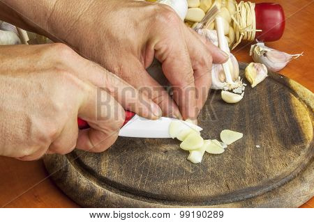 Ceramic knife chopping garlic preparation cooking. Garlic, aromatic ingredients for flavoring food.