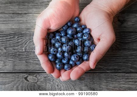 A Man Holds A Handful Of Blueberries On Wooden Background. Rustic Cozy Background With Healthy Food.