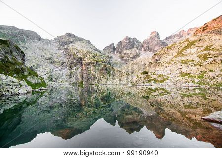 Rocky mountain peak by a lake at sunrise