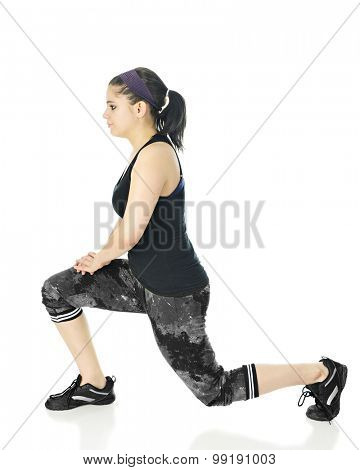Profile of an attractive teen girl doing lunges in her black and gray workout clothes.  On a white background.