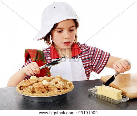 An adorable elementary baker slicing butter to put on the apple slices she has in her pie shell.  On a white background.
