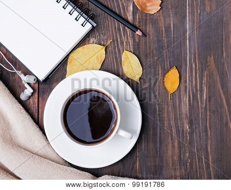 Coffee, Notepad, Pensil And Autumn Leaves On The Wooden Background