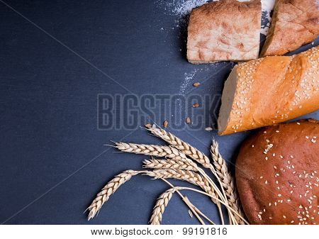 Different Kinds Of Bread And Wheat Ears On The Black Background