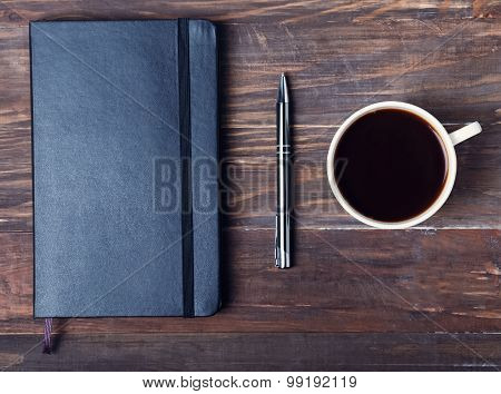 Black Notepad, Pen And Cup Of Black Coffee On The Wooden Table