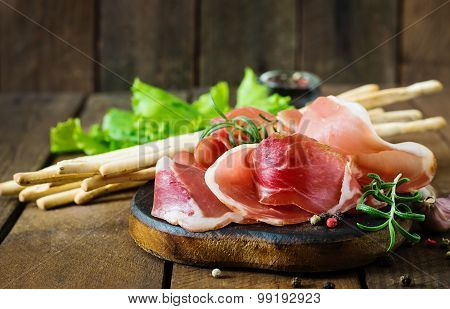 Grissini bread sticks with prosciutto on old wooden background