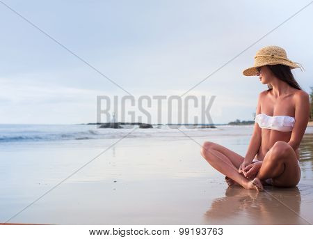 Young woman in bikini and straw hat enjoying her time in the evening at tropical beach