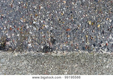 Rough asphalt structure with many colorful stones and concrete