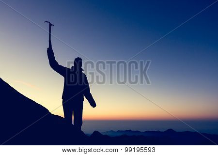 Silhouette of alpinist celebrating.