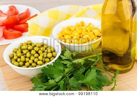 Tomatoes, Green Peas, Corn, Parsley And Olive Oil On Board