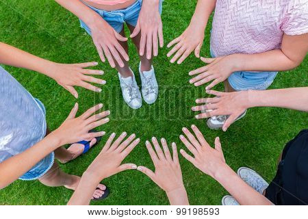Many Children Hands Joining In Circle Above Grass