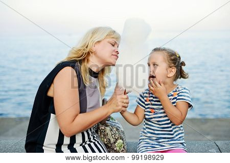 Woman And Little Girl Eating A Cotton Candy