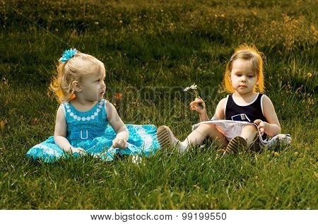 Two Little Sisters Sitting In The Grass