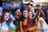 party, technology, nightlife and people concept - smiling friends with smartphone taking selfie in c poster