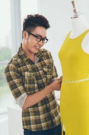 picture of dress mannequin  - Vietnamese dressmaker measuring a mannequin in yellow dress - JPG