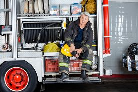 picture of firemen  - Full length portrait of confident fireman sitting in truck at fire station - JPG