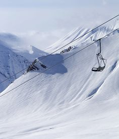 foto of lifting-off  - Chair lift at ski resort and off piste slope - JPG