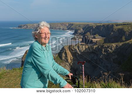 Active old lady pensioner by beautiful coastal view in summer