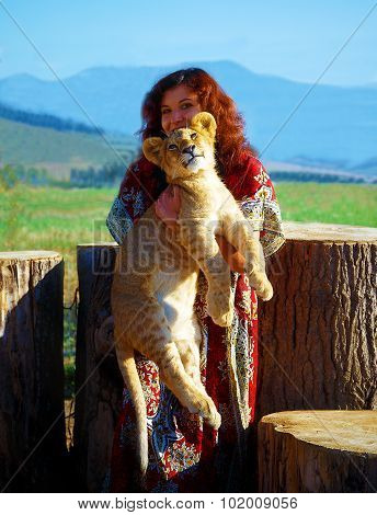 young woman with ornamental dress l playing with lion cub in nature. woman holding lion cub.