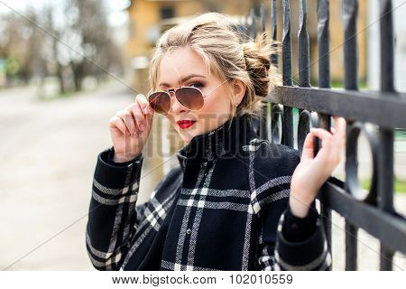 Nice Girl In Black Coat And Sunglasses Standing Near A Wrought Iron Fence