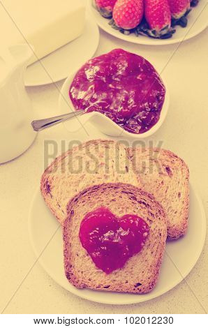 jam forming a heart on a toast, on a table set for breakfast, with a filter effect