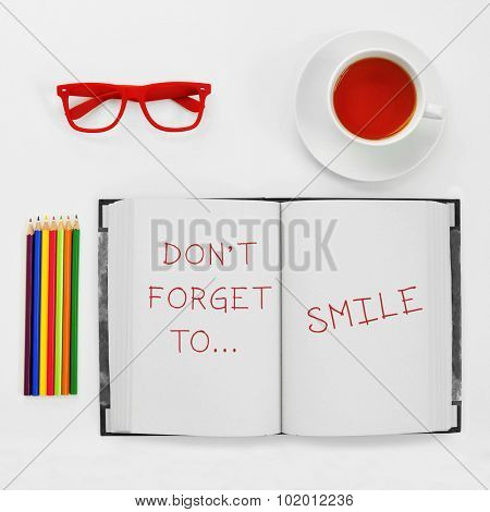 high-angle shot of a some colored pencils, a pair of red plastic-rimmed eyeglasses, a cup of tea and a notebook with the text dont forget to smile, on a white table