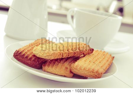 closeup of a plate with a pile of homemade biscuits and a cup of coffee or tea on the kitchen table