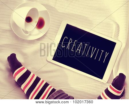 high-angle of the feet of a man wearing striped socks, a cup of coffee and a tablet computer with the word creativity in its screen, on a bed covered with a white bedcover, filtered