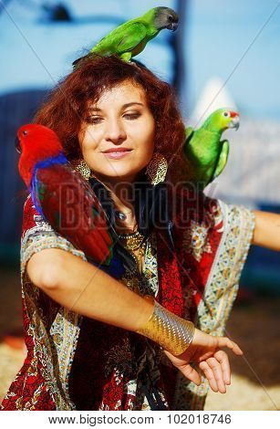 Young woman in ornamental dress and beautiful gold jewelry with a color parrots