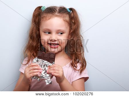 Curious Cute Kid Girl Eating Dark Chocolate And Looking Fun. Closeup Portrait