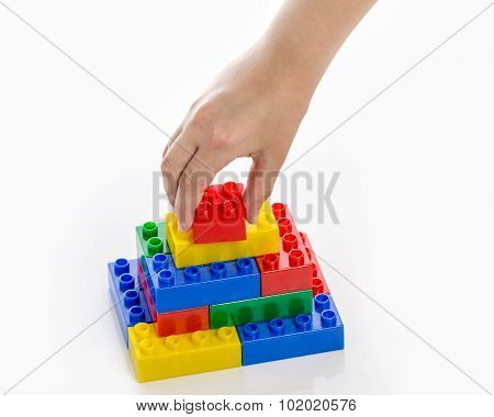 Hand Completing Colorful Plastic Brick Structure