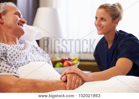 Nurse Talking To Senior Male Patient In Hospital Bed