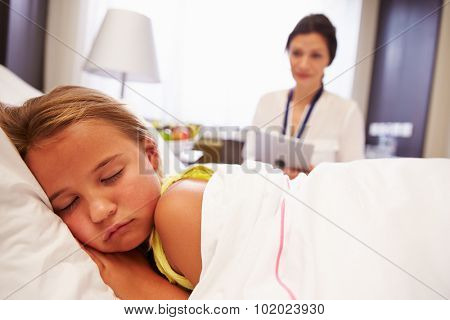 Doctor Observing Sleeping Child Patient In Hospital Bed