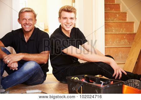 Two men sitting on wooden floor during a house refurbishment