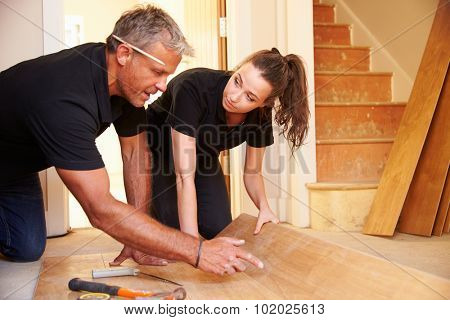 Man and woman laying wood panel flooring in a house