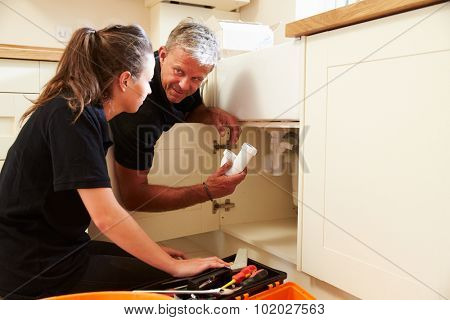 Plumber showing female apprentice how to fit a kitchen sink