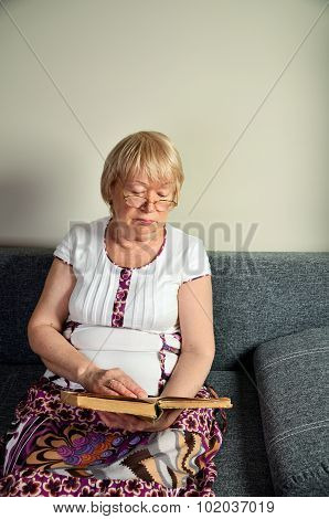Elderly Woman Reading A Book Sitting On The Couch Vertical