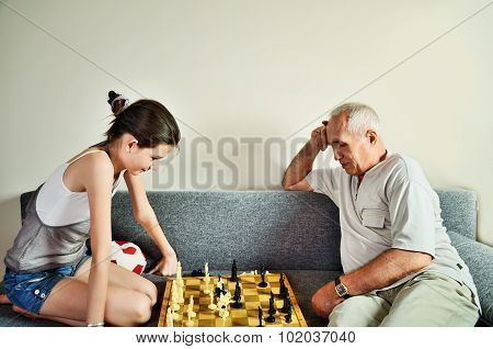 Granddaughter And Grandpa Playing Chess Front View