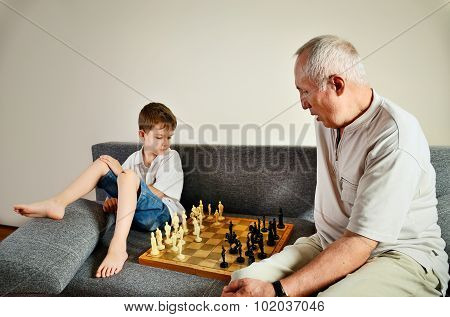 Grandson And Grandpa Playing Chess