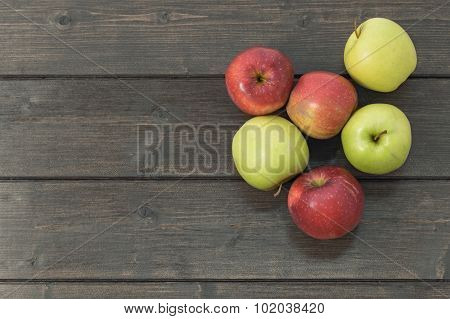 Red And Green Apples On A Wooden Desk