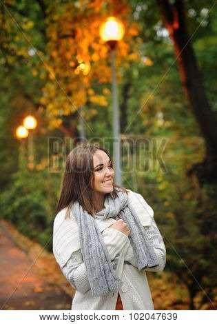 Autumn outdoor portrait of a smiling woman wearing knitted jacket.