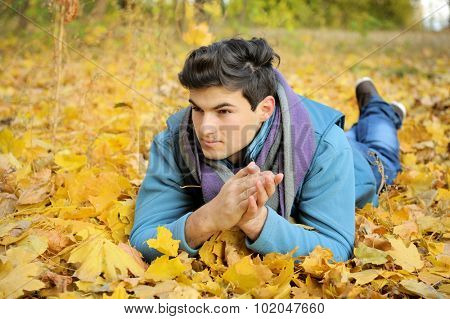 Young handsome lying in foliage man, autumn otdoor.